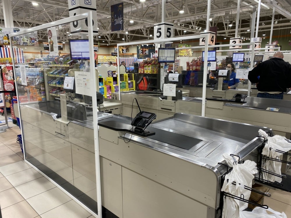 Plexiglass barriers shield cashier stations in grocery store checkout lanes.