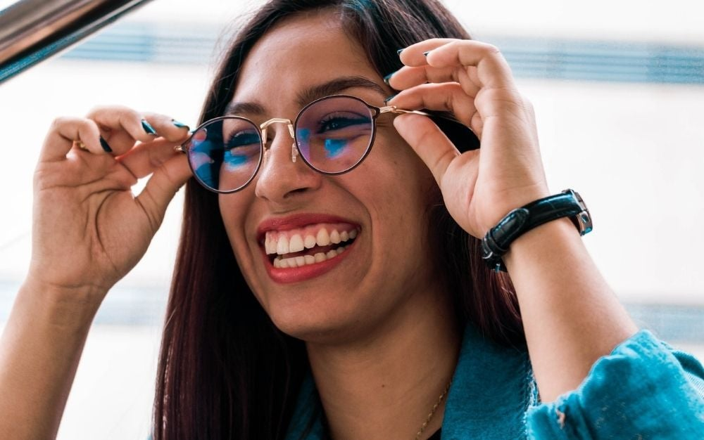 A girl with long brown hair who is smiling with her teeth out as she puts on a pair of oval-shaped glasses with black and gold skeleton.