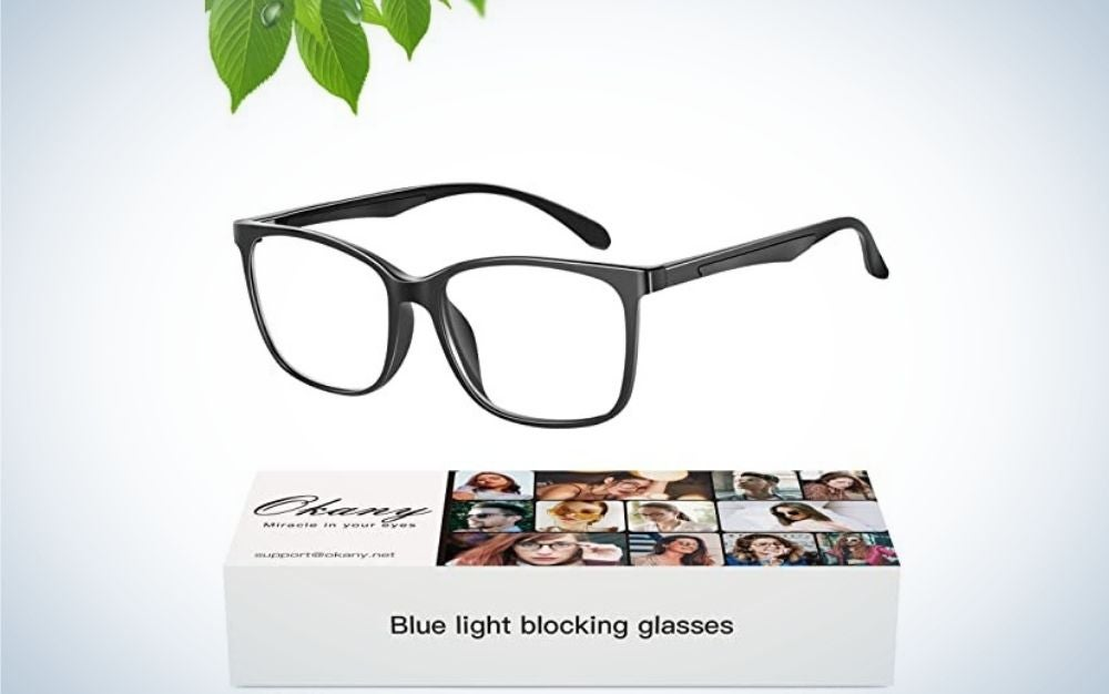 A pair of glasses with a classic black frame and translucent glass, placed on the side and below them in a white box which has the brand name and small demonstration photos on it.