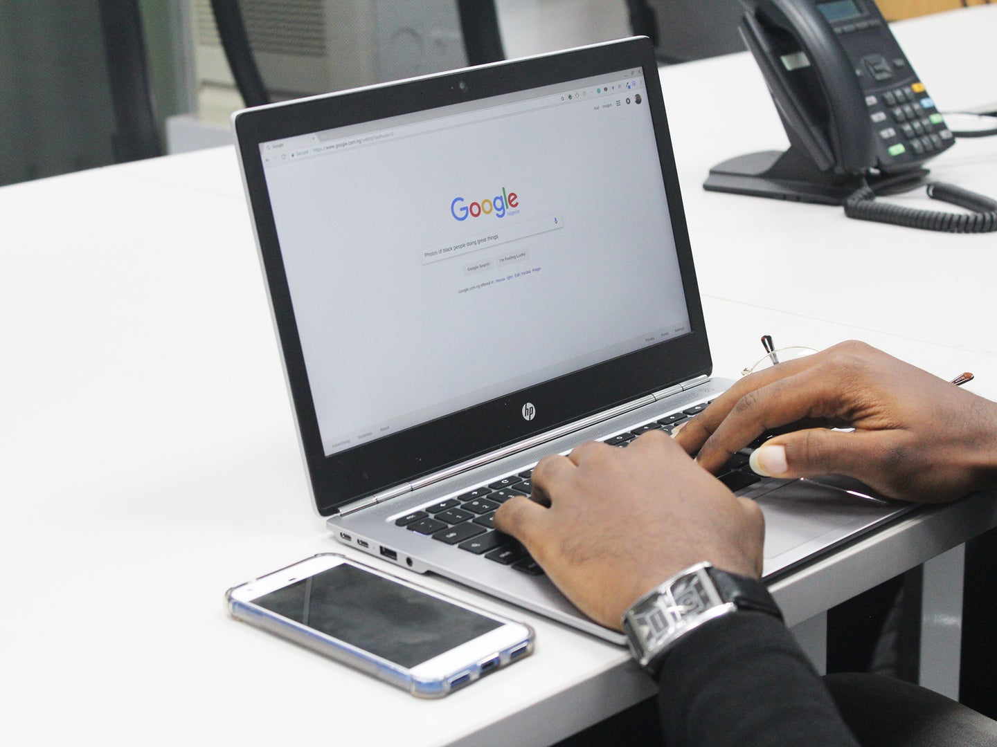 A person using a laptop computer with Google on the screen.