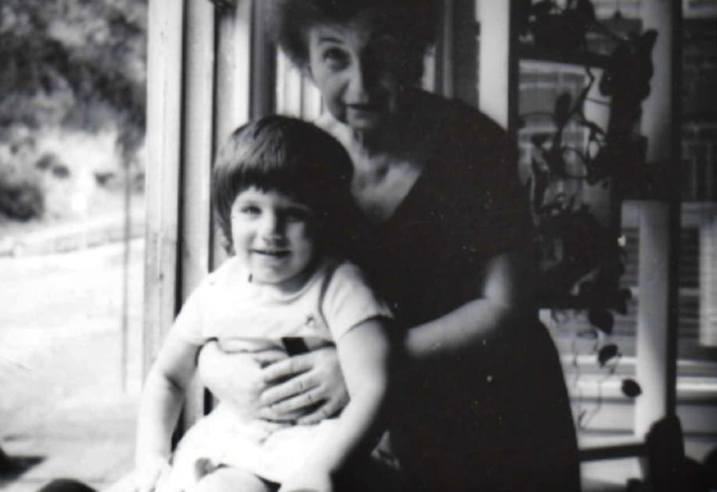 Toddler with grandmother near window in black and white photo