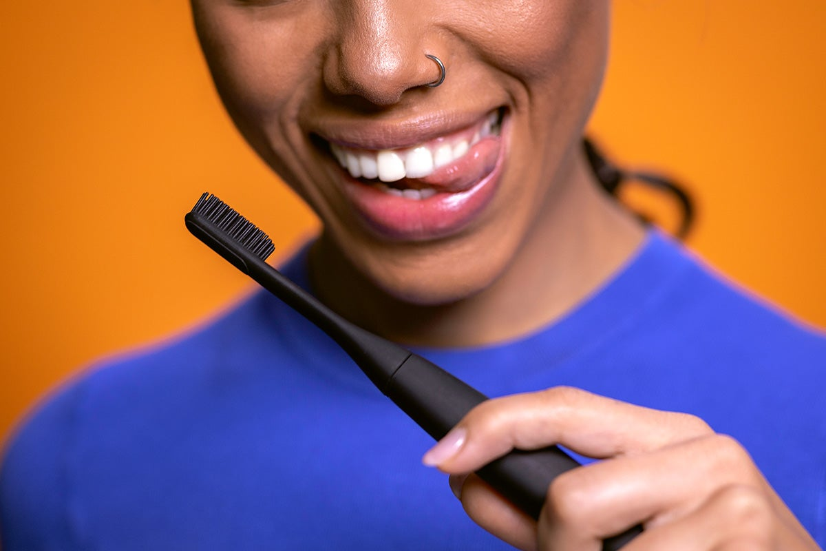 Woman smiling and holding toothbrush