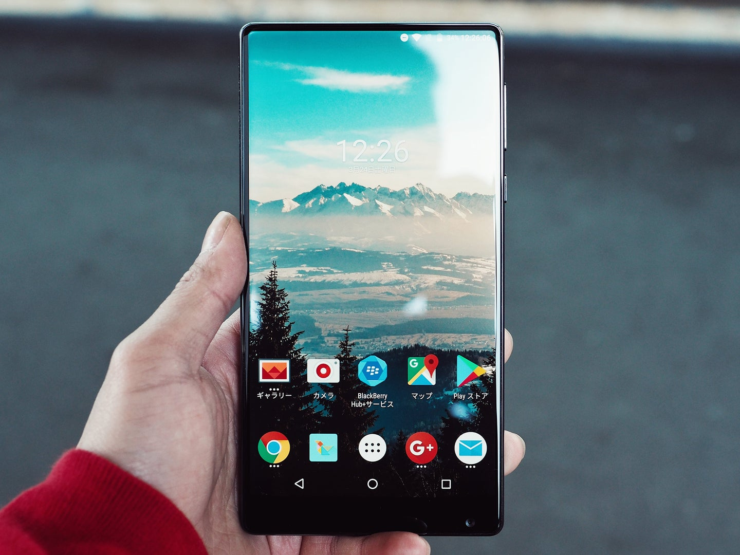 A person holding an Android phone with a live background.