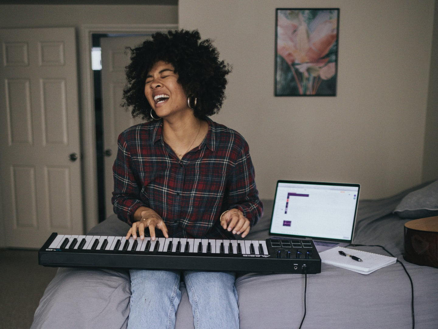 A person sitting on a bed, enjoying playing a keyboard that's hooked up to a laptop.