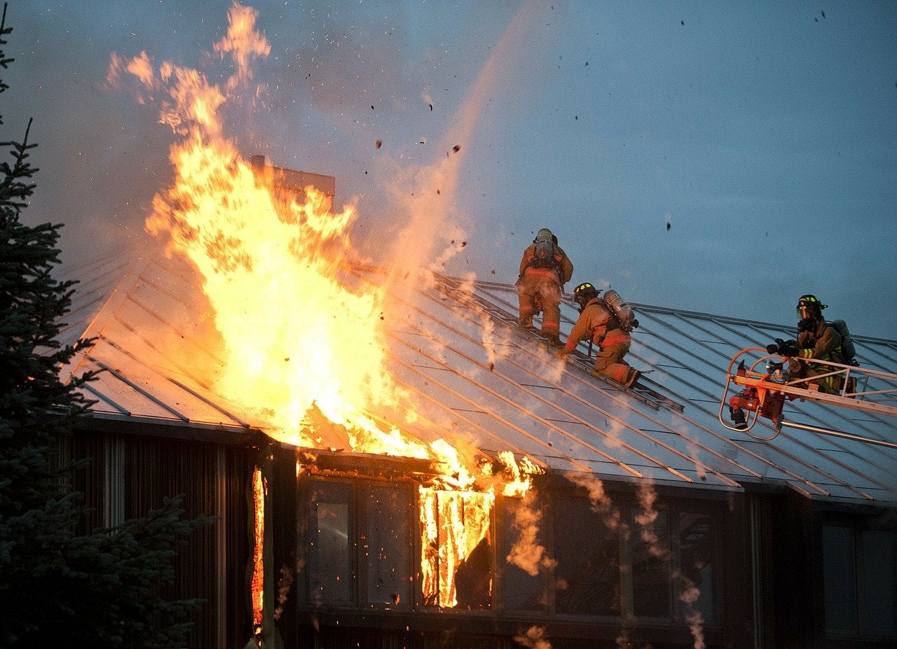 Firefighters battle a fire while climbing on a roof.