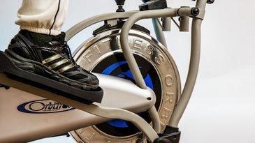 A foot of a person wearing sports sneakers who is pedaling on a black and white fitness machine.