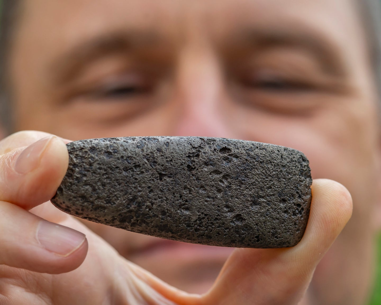 researcher holds up metal chickasaw artificat