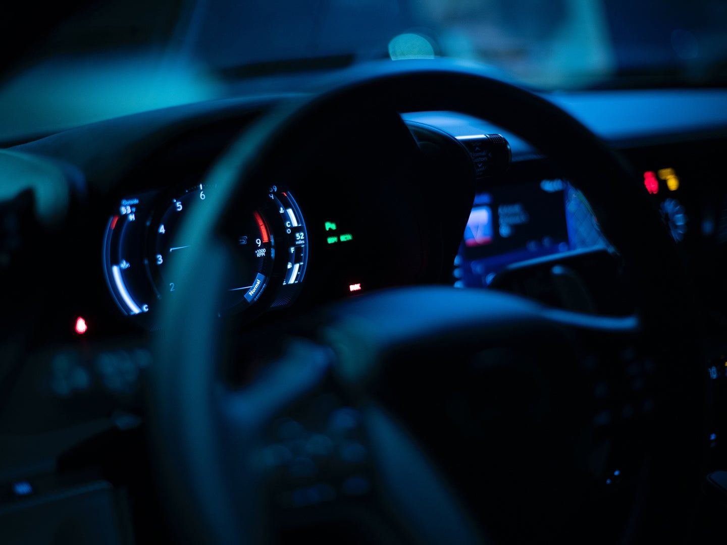 The steering wheel and dashboard of a car at night.
