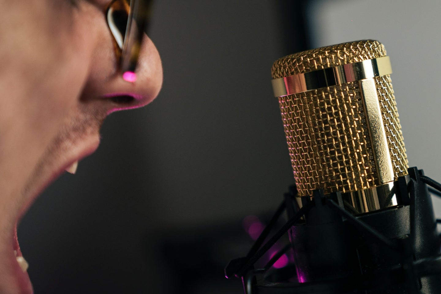 man yells at condenser mic with a gold grill
