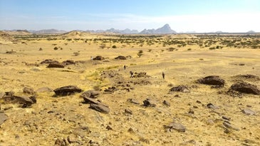 desert landscape dotted by qubbas or tombs