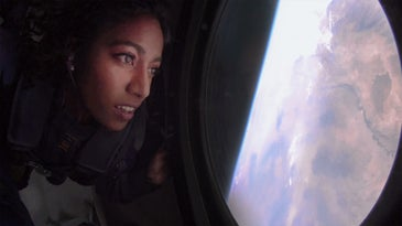 A woman's face partially in shadow, aboard a suborbital, looks out a window back at Earth.