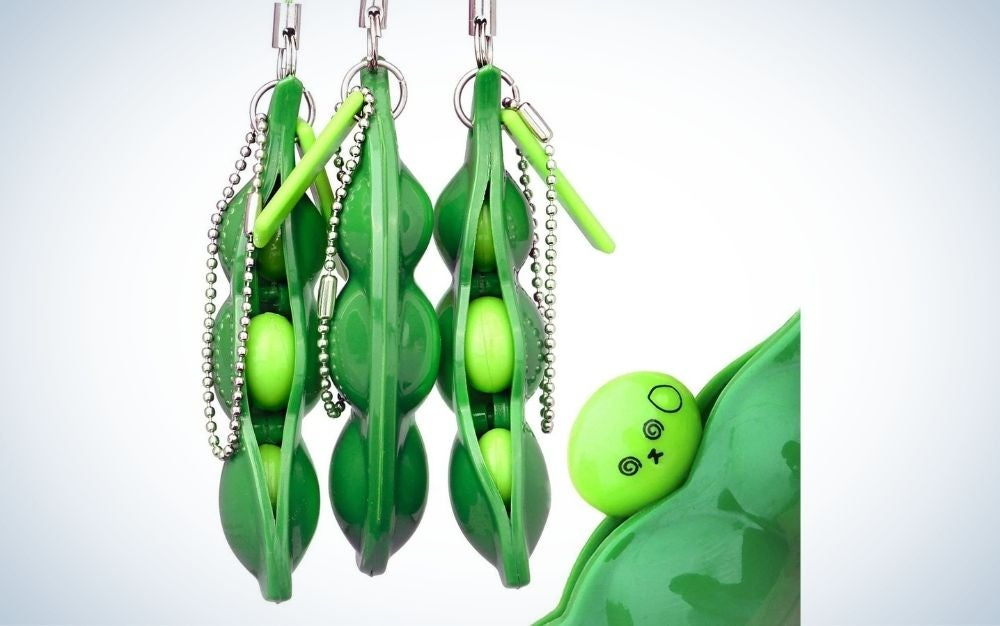 Three hanging and open beans chain with a strong green color and a squishy pea pod stress toy next to them.