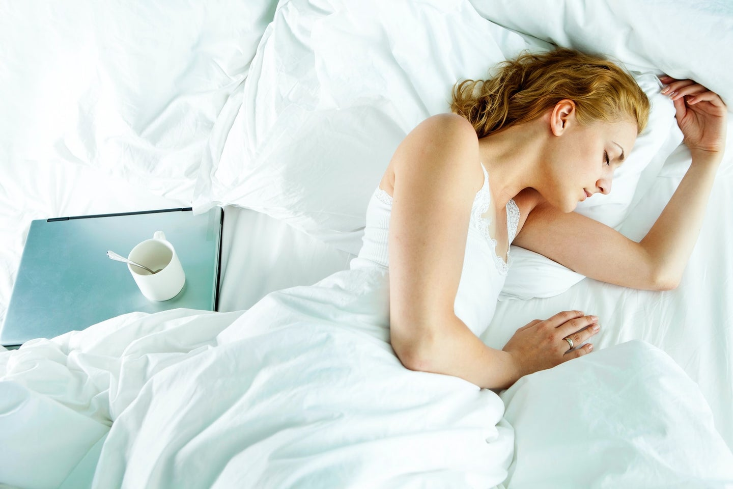 Woman sleeping in bed next to laptop and empty mug