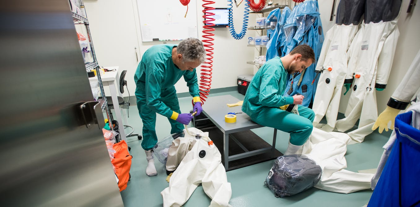 Two scientists changing out of PPE in a disease lab