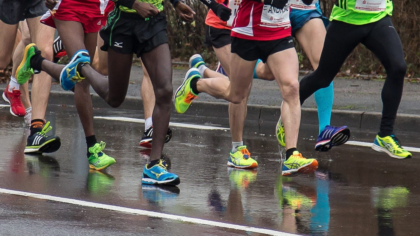 11 people are pictured running in a group on a rain-slicked road from the waist down. Most are wearing black shorts, the leader is wearing black, full length leggings. Their legs are muscular and their shoes are all bright colors like neon greens, blues, cherry red, and purple.