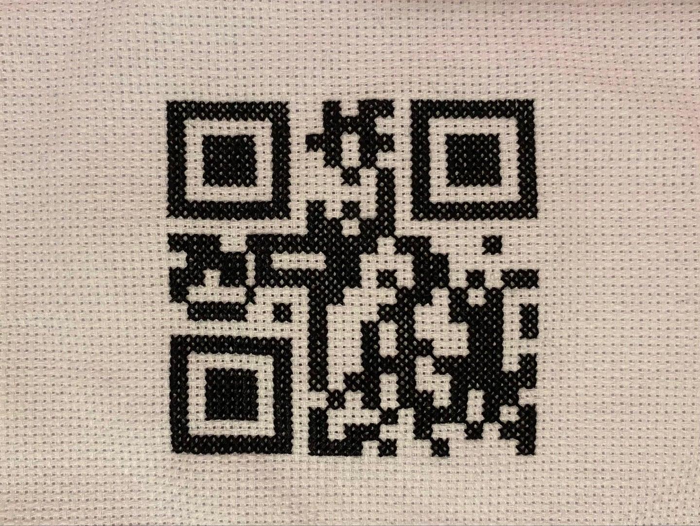 A cross-stitched QR code.