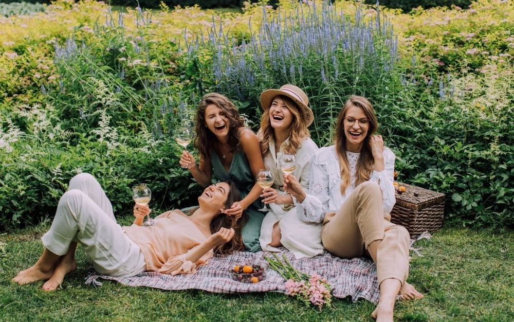 Four girls sitting and smiling with each other while in their hands are wine glasses.