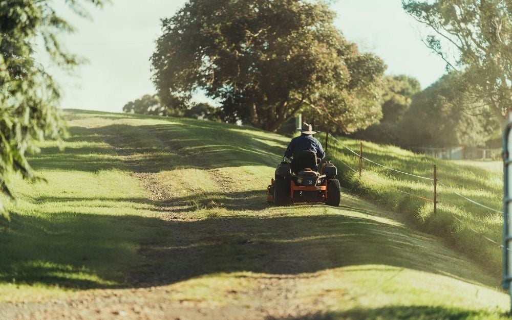 A man riding a mower in the middle of a green grass field with sunlight falling on it.