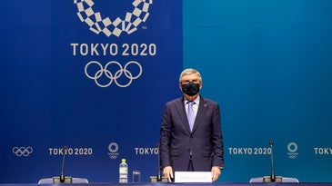 A grey haired man in a dark suit, wearing a black mask stands in from of a two-toned blue background and behind a long table set up with three microphones and chairs. The background says