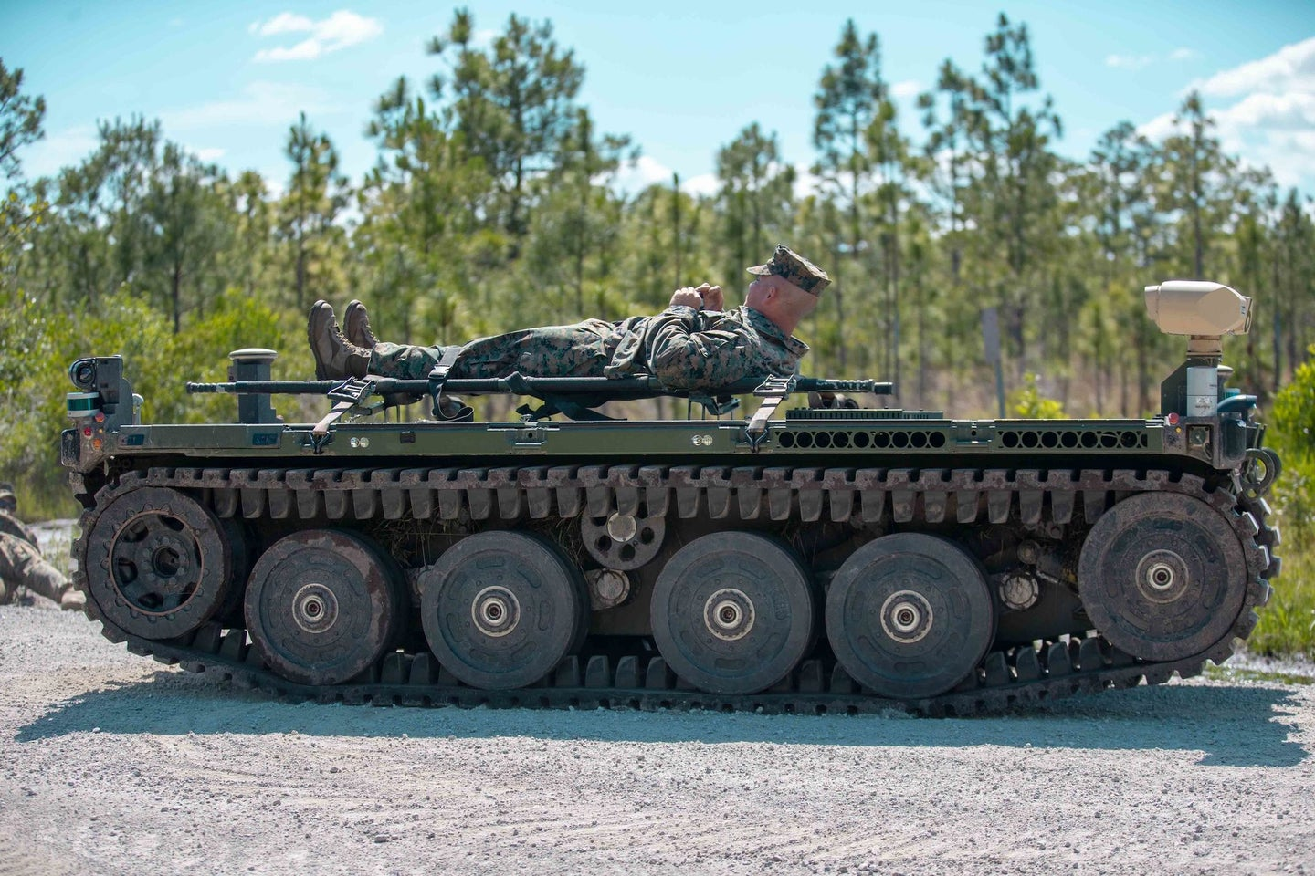 A Marine lies on top of a robotic vehicle on treads.