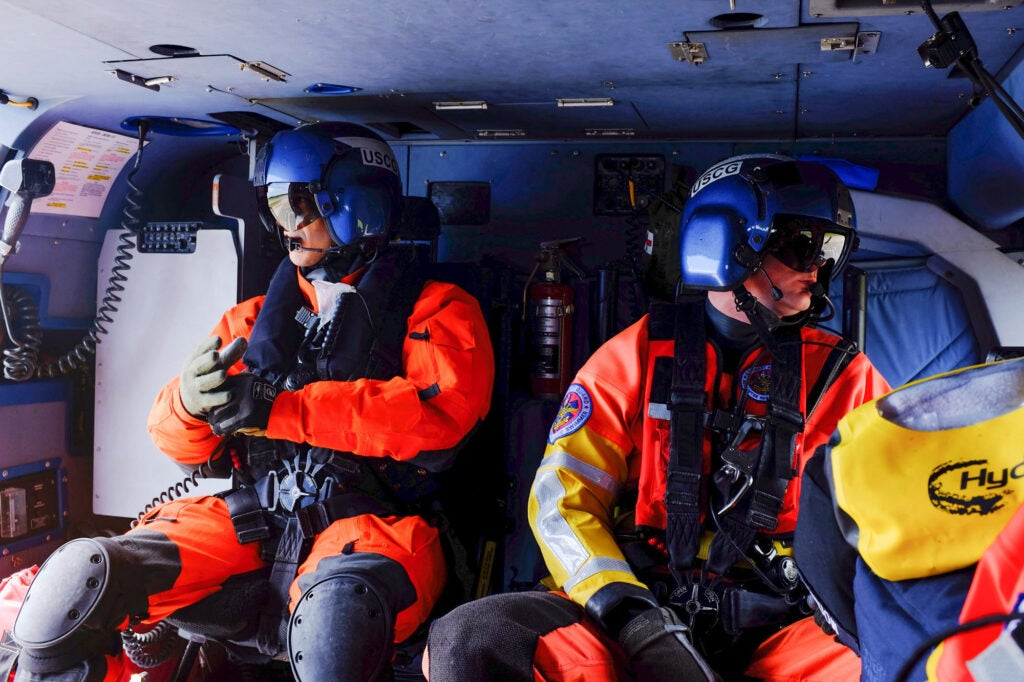Two members of the Coast Guard ride in the back of a helicopter