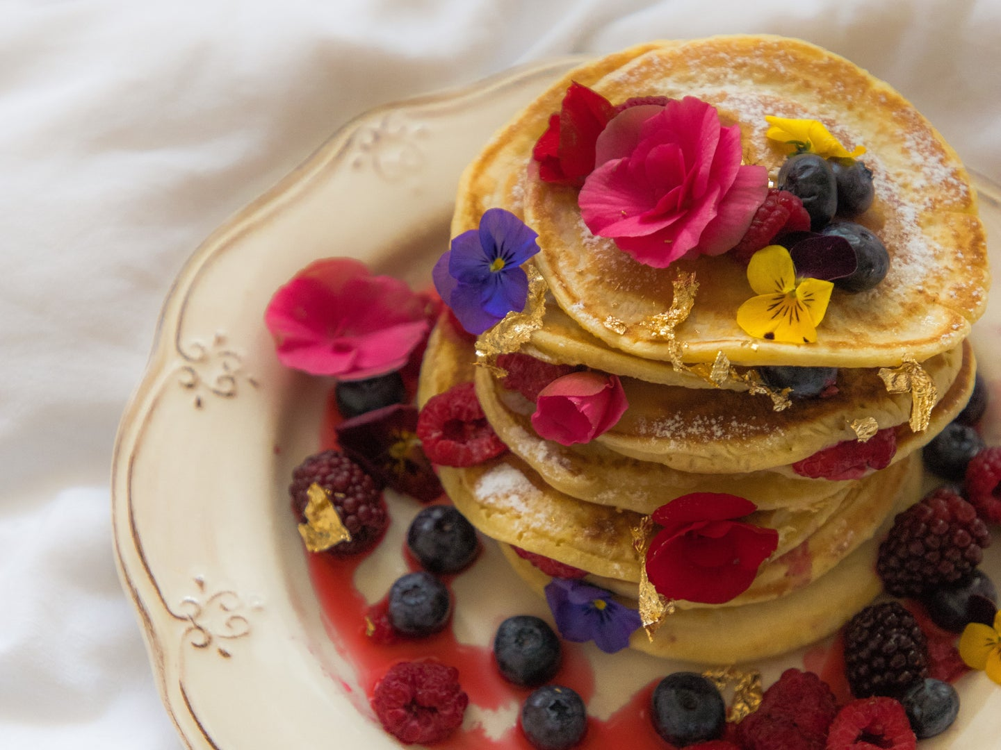 A stack of pancakes topped with berries and edible flowers, on a white plate atop a white tablecloth.