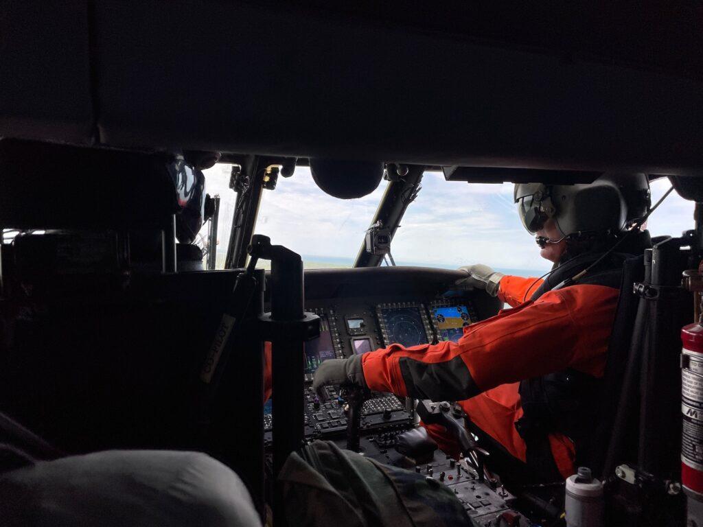 A pilot flies a Coast Guard helicopter