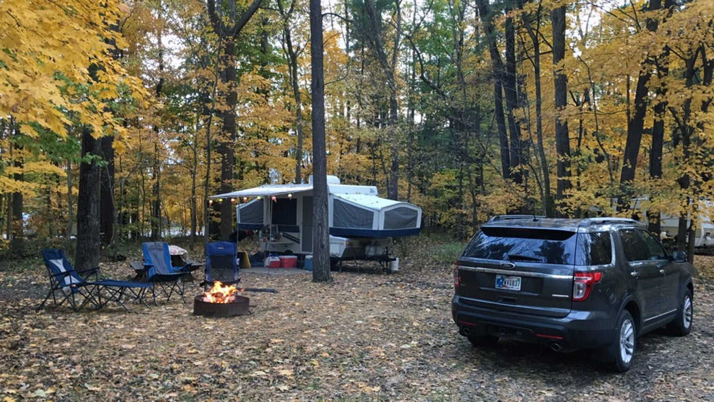 Pop-up camper in the woods next to an SUV and firepit