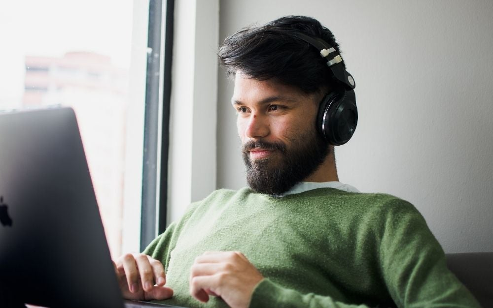 A young man with dark hair and beard and a pair of black headphones placed in his ear and a laptop in front of him.