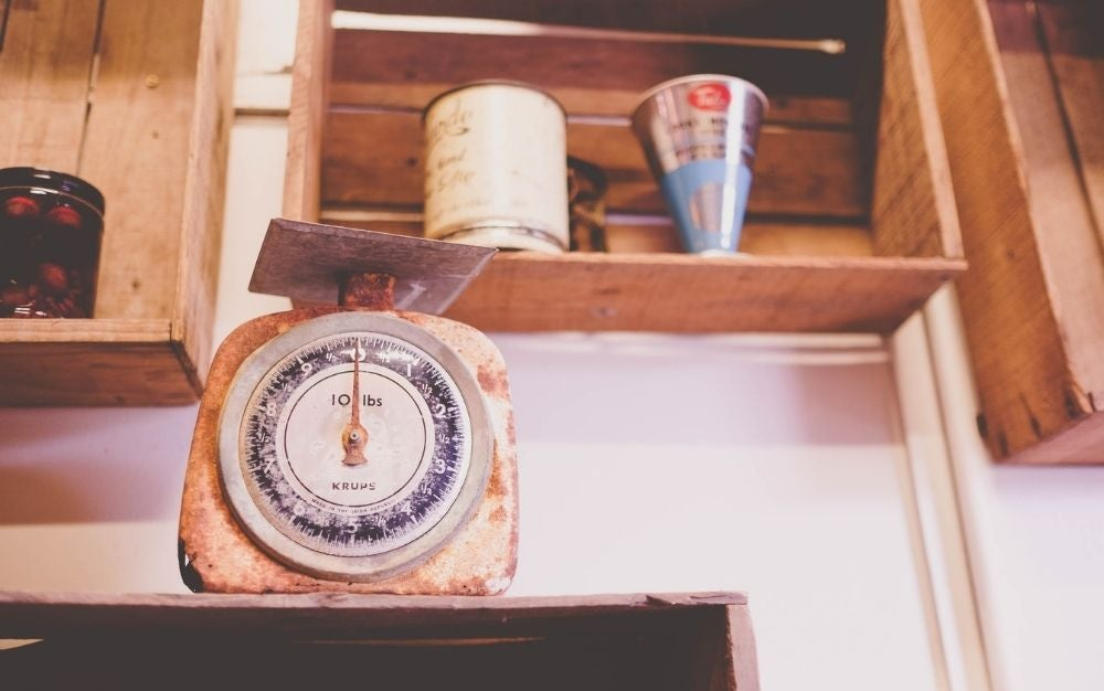 An old wooden weight gauge placed on a wooden drawer below some other drawers.