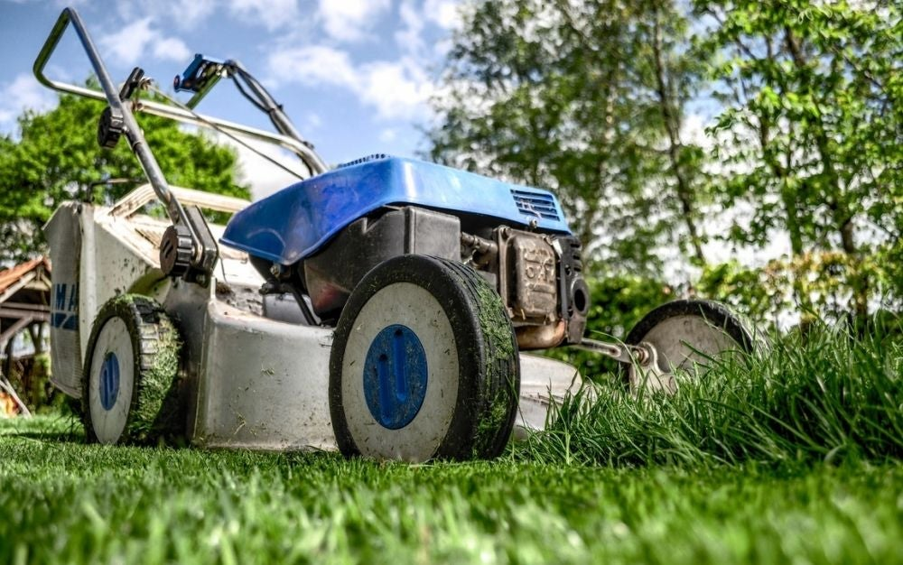 A grey and blue lawn mower photographed from its tire corner, on a field of green grass.