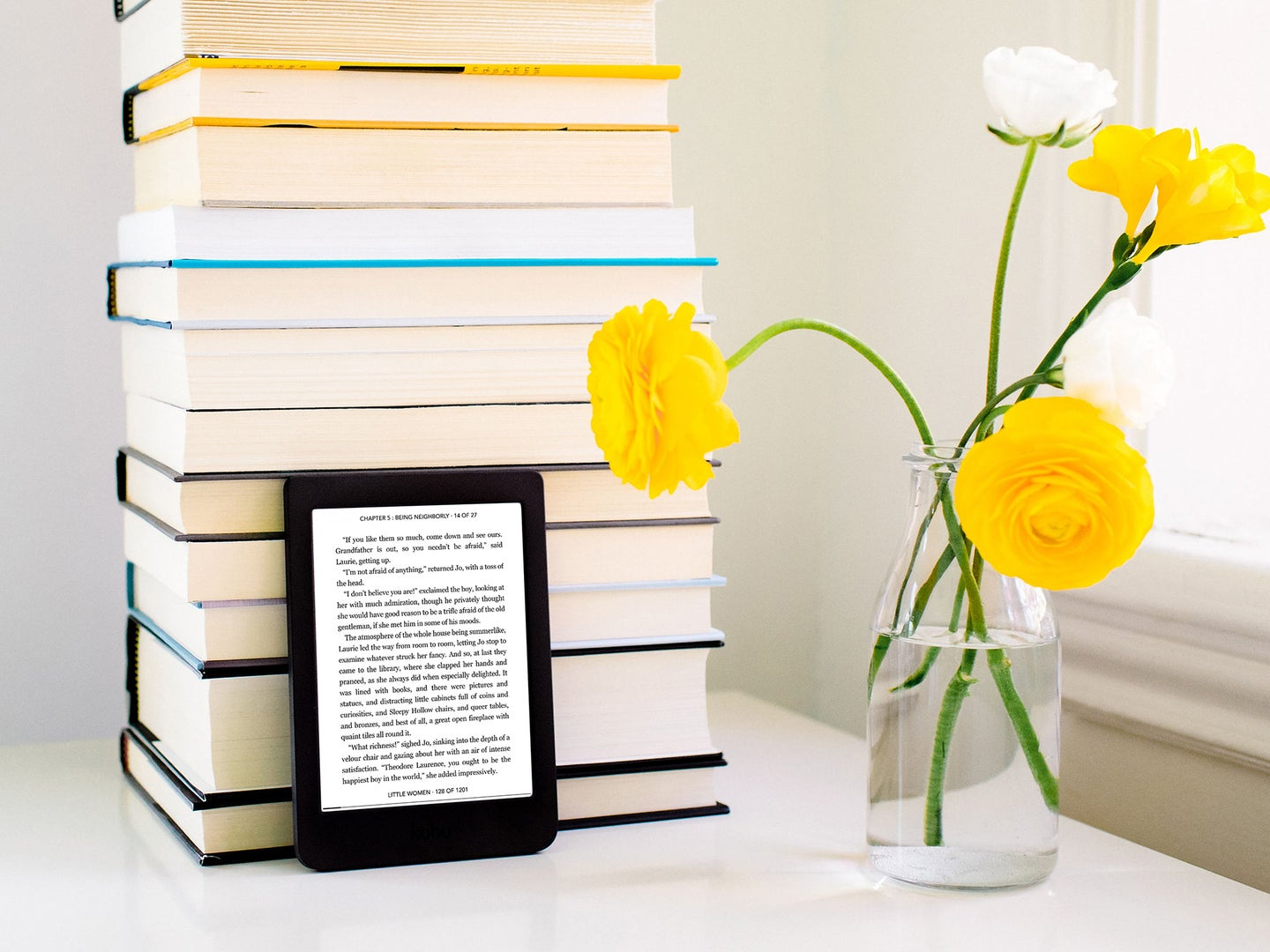 A Kobo e-reader leaning against a stack of books next to a glass jar with yellow flowers in it.