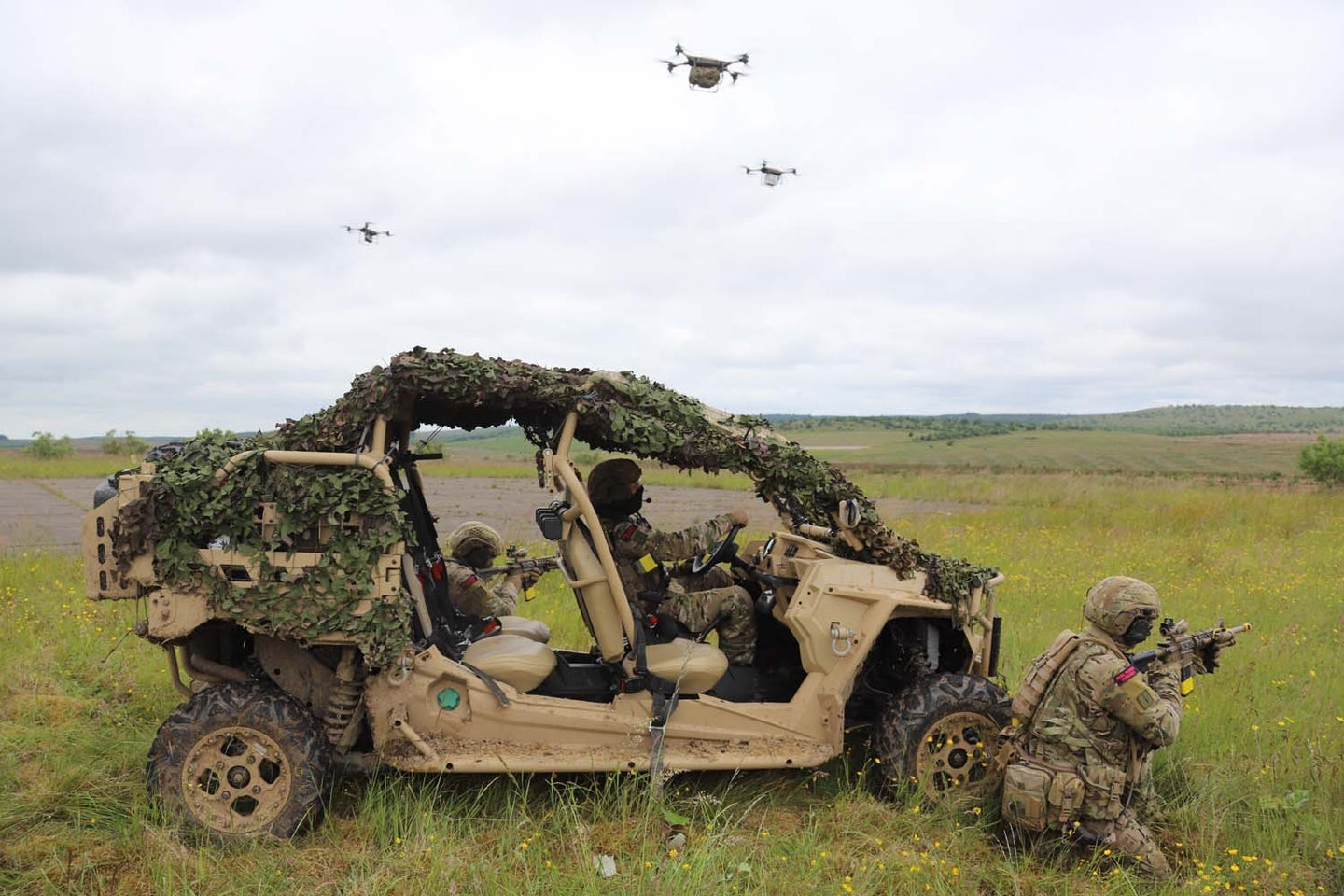soldiers near a vehicle with drones in the background