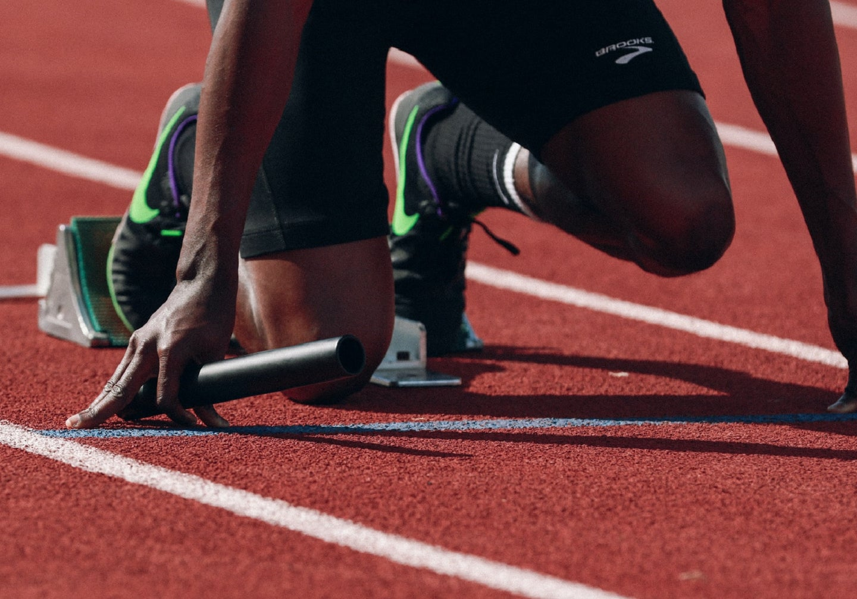 Track runner kneeling on starting line