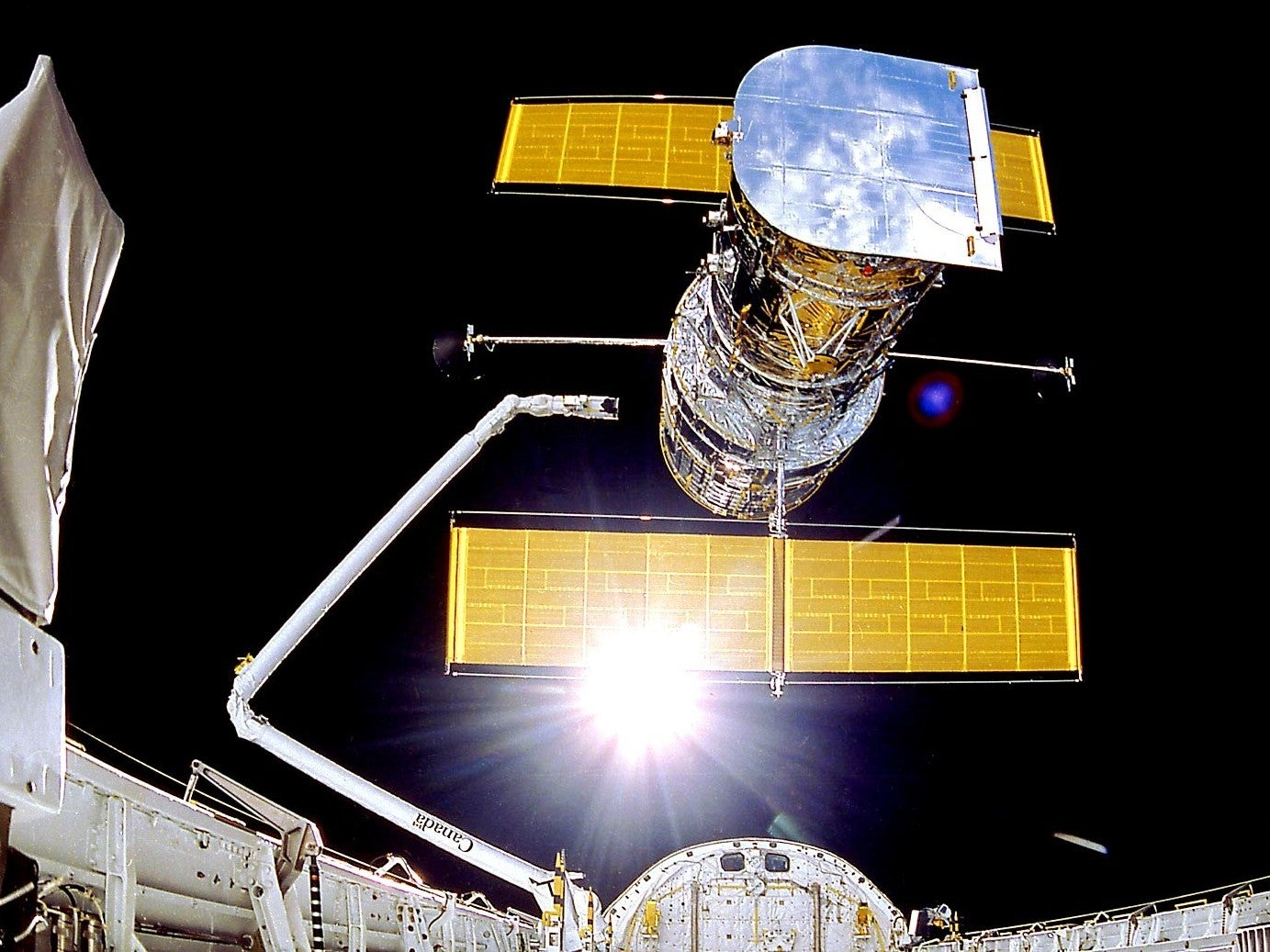 The Hubble Space Telescope, with its yellow solar panels featured prominently.