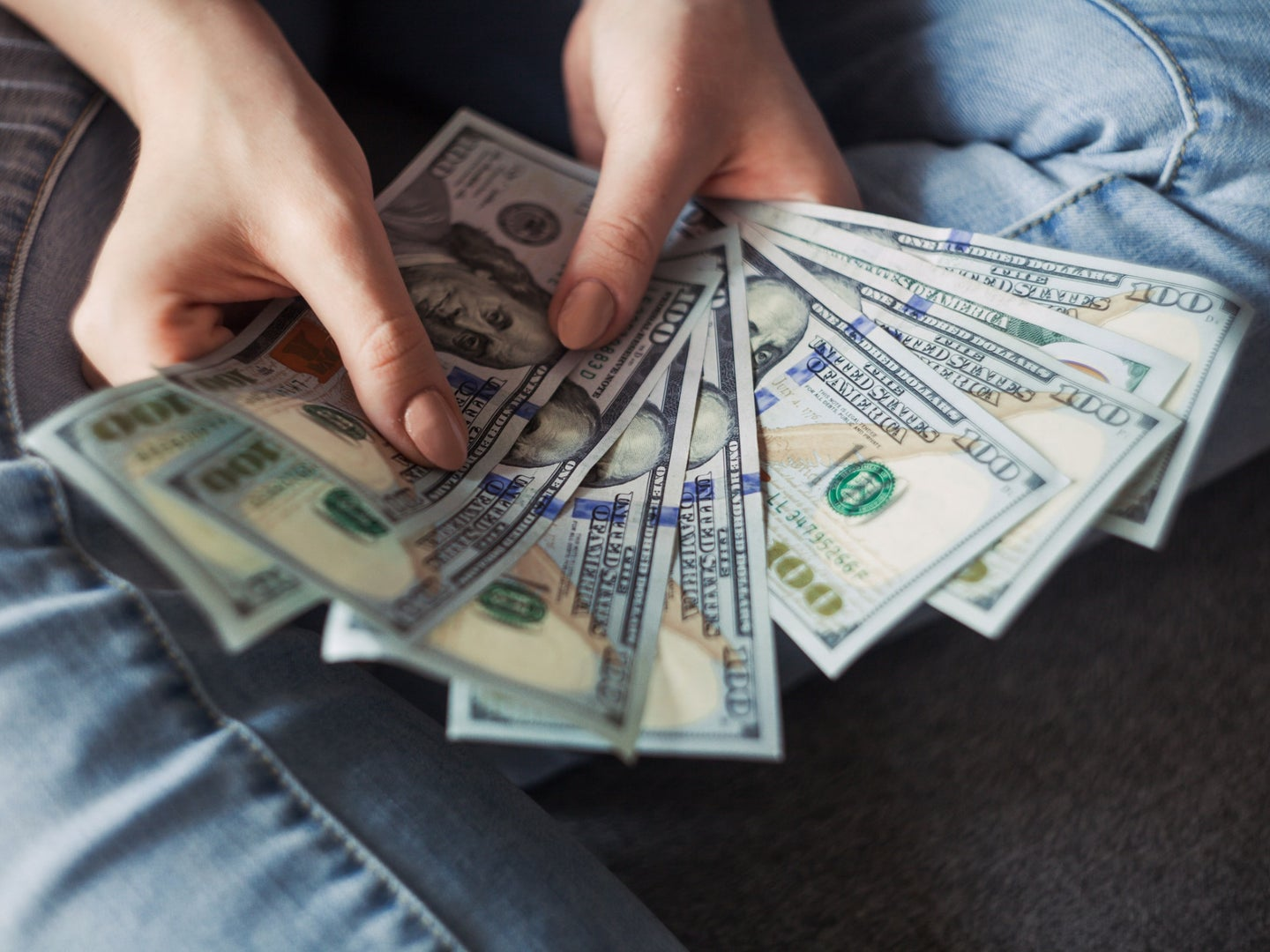 A person sitting on the floor, holding several $100 bills in a fan shape.