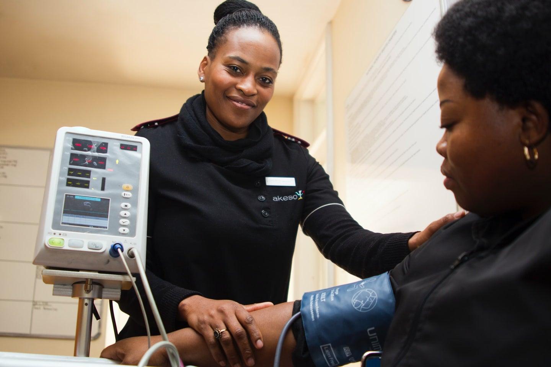 Black health care worker reading blood pressure on Black patient
