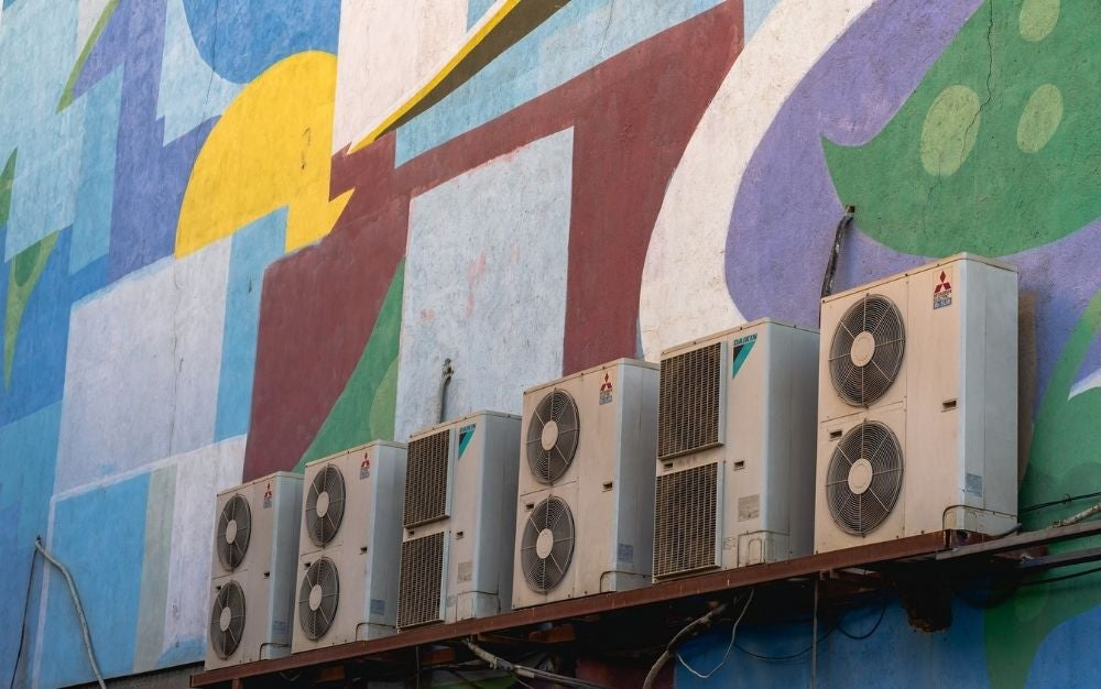 Best window air conditioner models lined up next to each other on a colored wall painted on it.