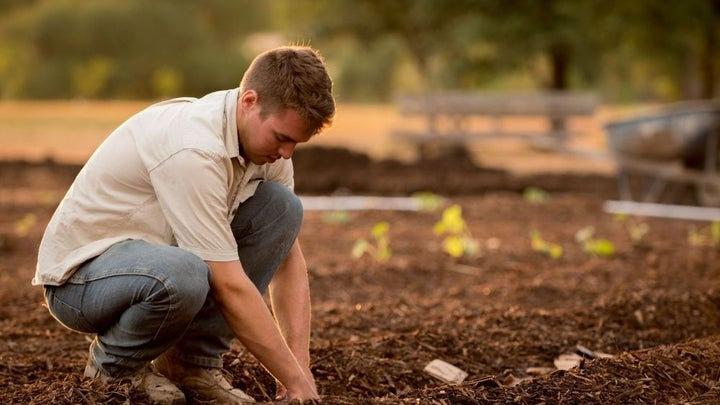 A man with white skirt and jeans planting in an empty land with soil.