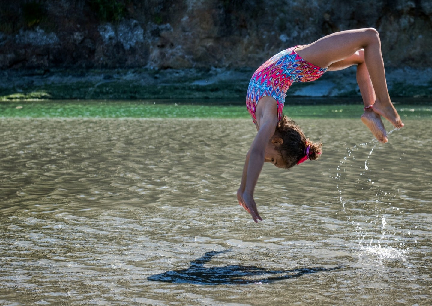 Kid in pink bathing suit doing a flip in a lake