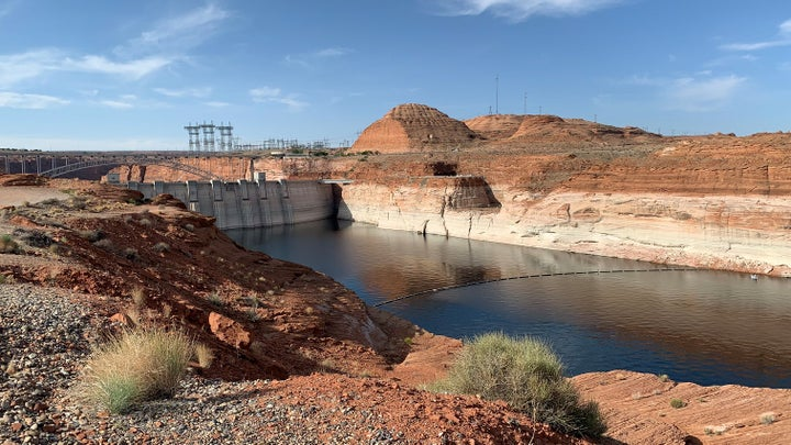 A dam on Lake Powell displays a chalky white bathtub-like ring that shows how much water reservoir levels have declined amid an ongoing drought.