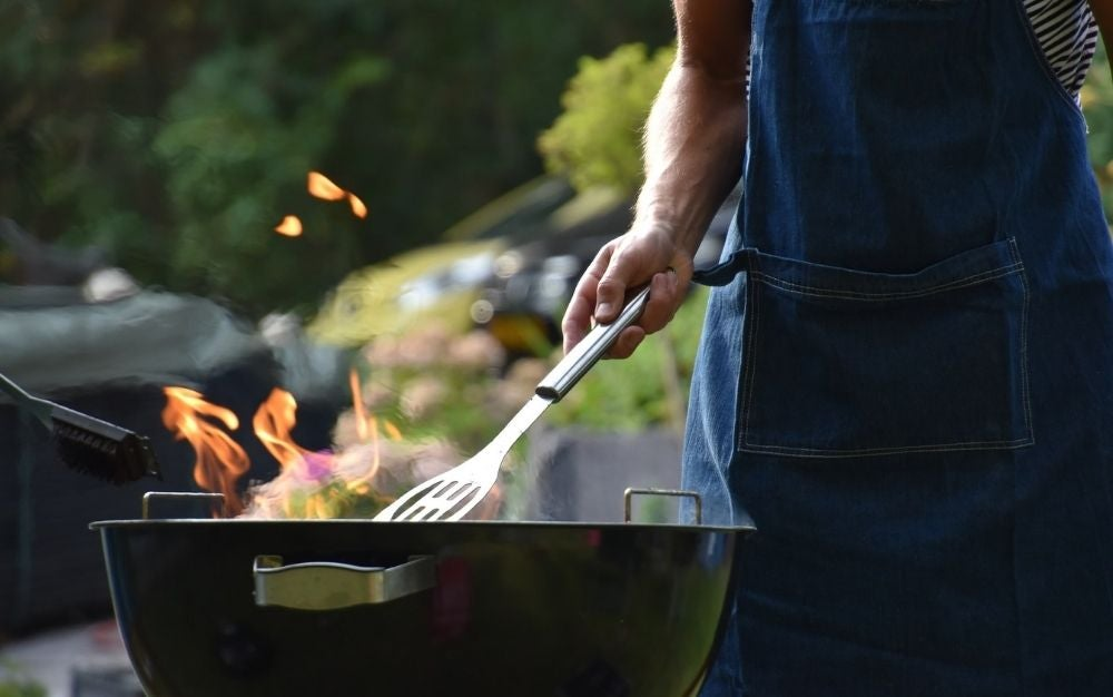 A man hand with a big silver fork for grilling into a black grill with a flame into it outside a yard.