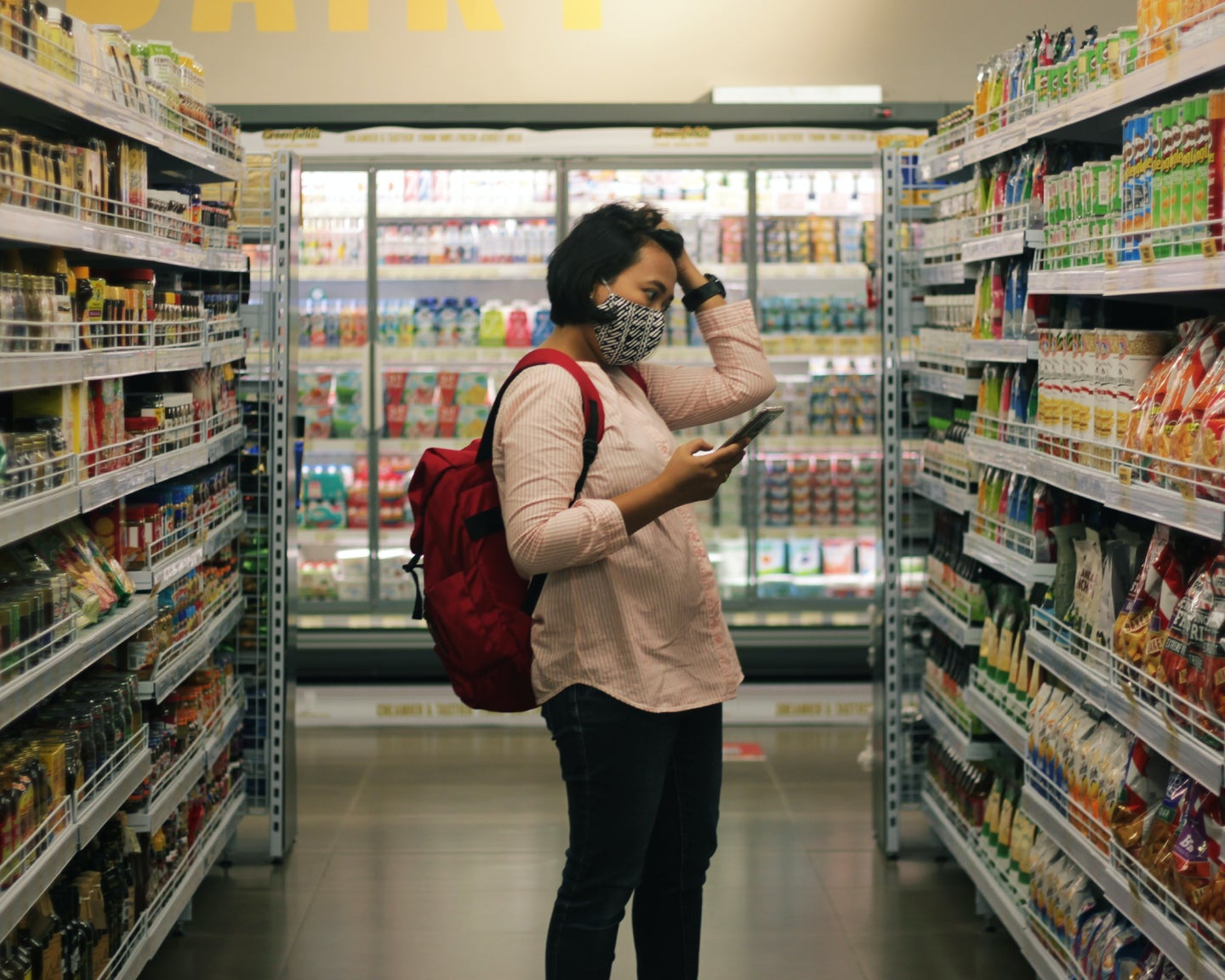 A dark haired person wearing a black and white patterned mask with a red backpack stands in a grocery store aisle, holding up a smartphone in one hand and running their other hand through their hair. They are looking intently at an array of colorful packaged foods.