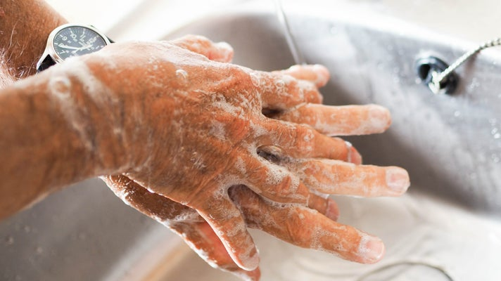A person washing their hands with soap and water spreads soap between their fingers over the basin of a sink.
