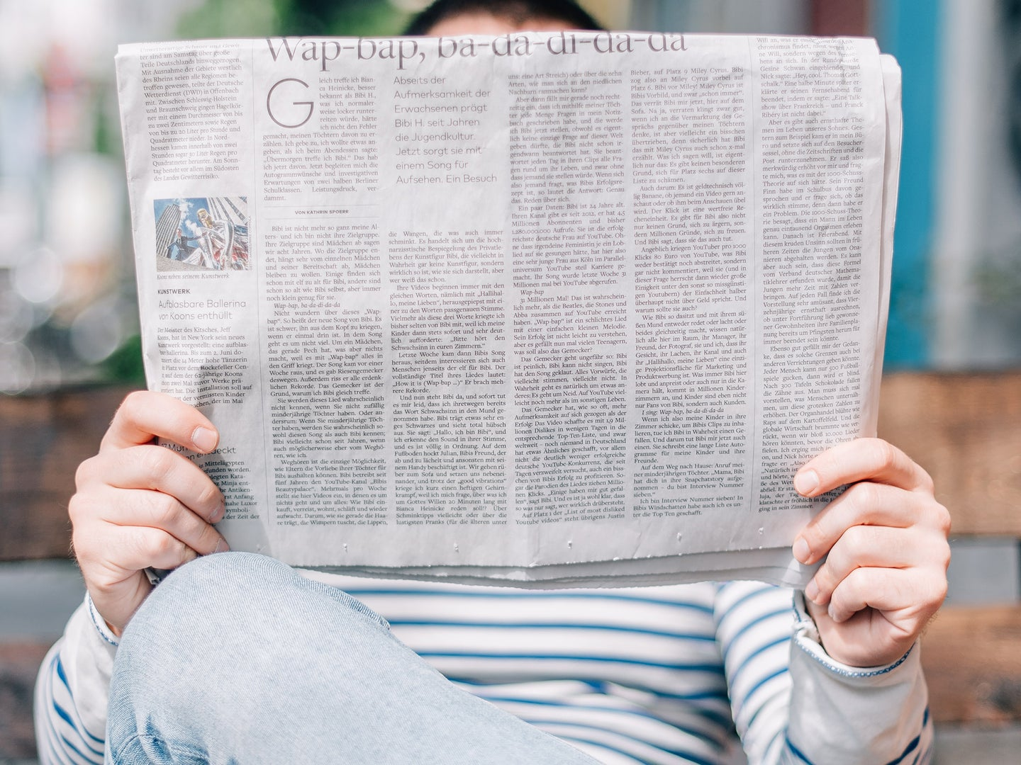 person holding open newsletter covering face