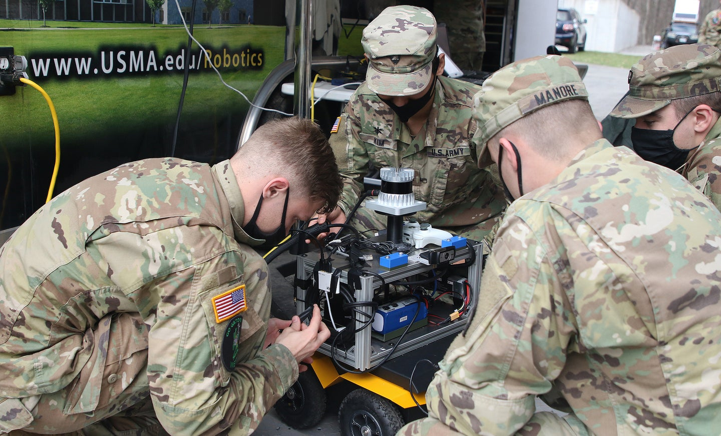 Soldiers work on a robot