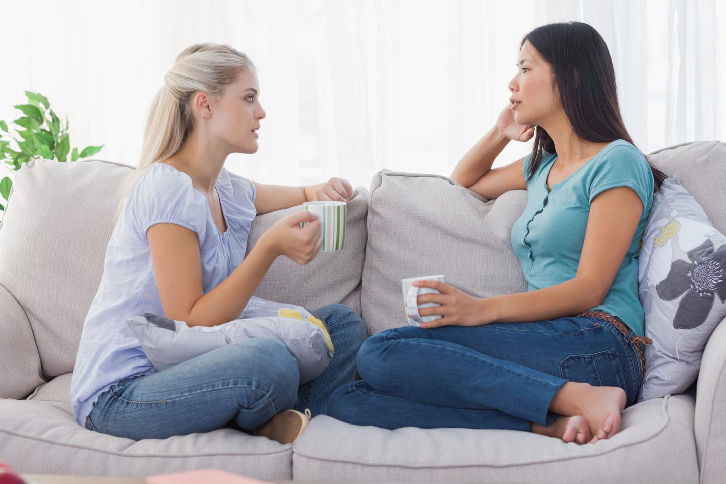 Two women sit cross-legged, facing each other on a beige sofa. They are each holding a white mug and look absorbed in conversation.