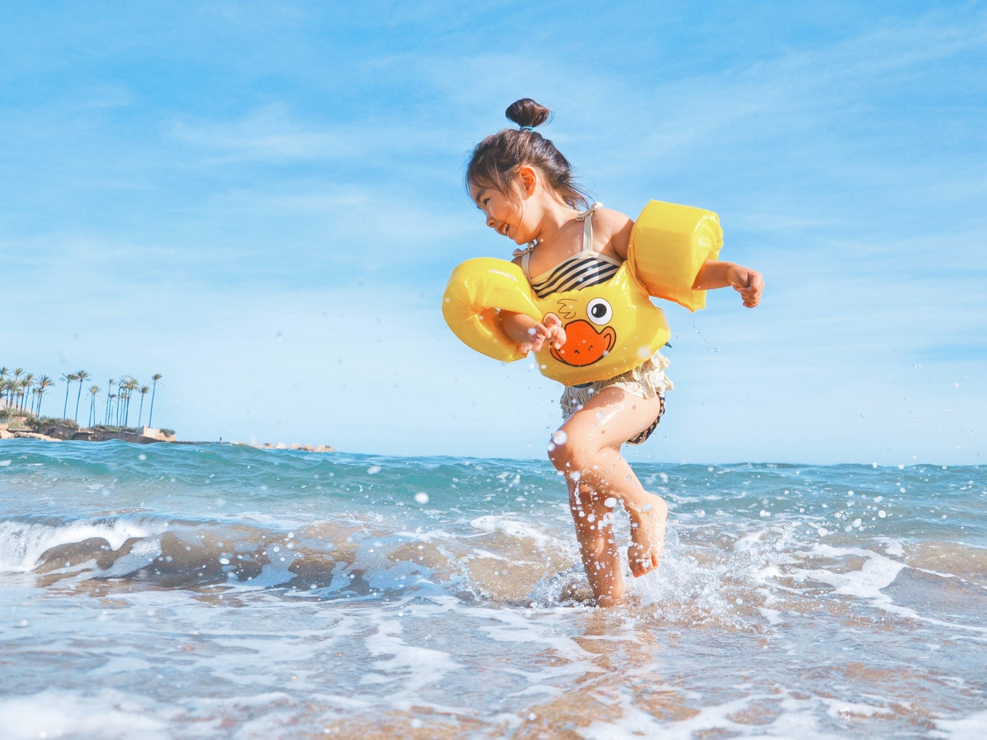 A small child wearing floaties on their arms and waist while playing in the surf of a tropical beach.