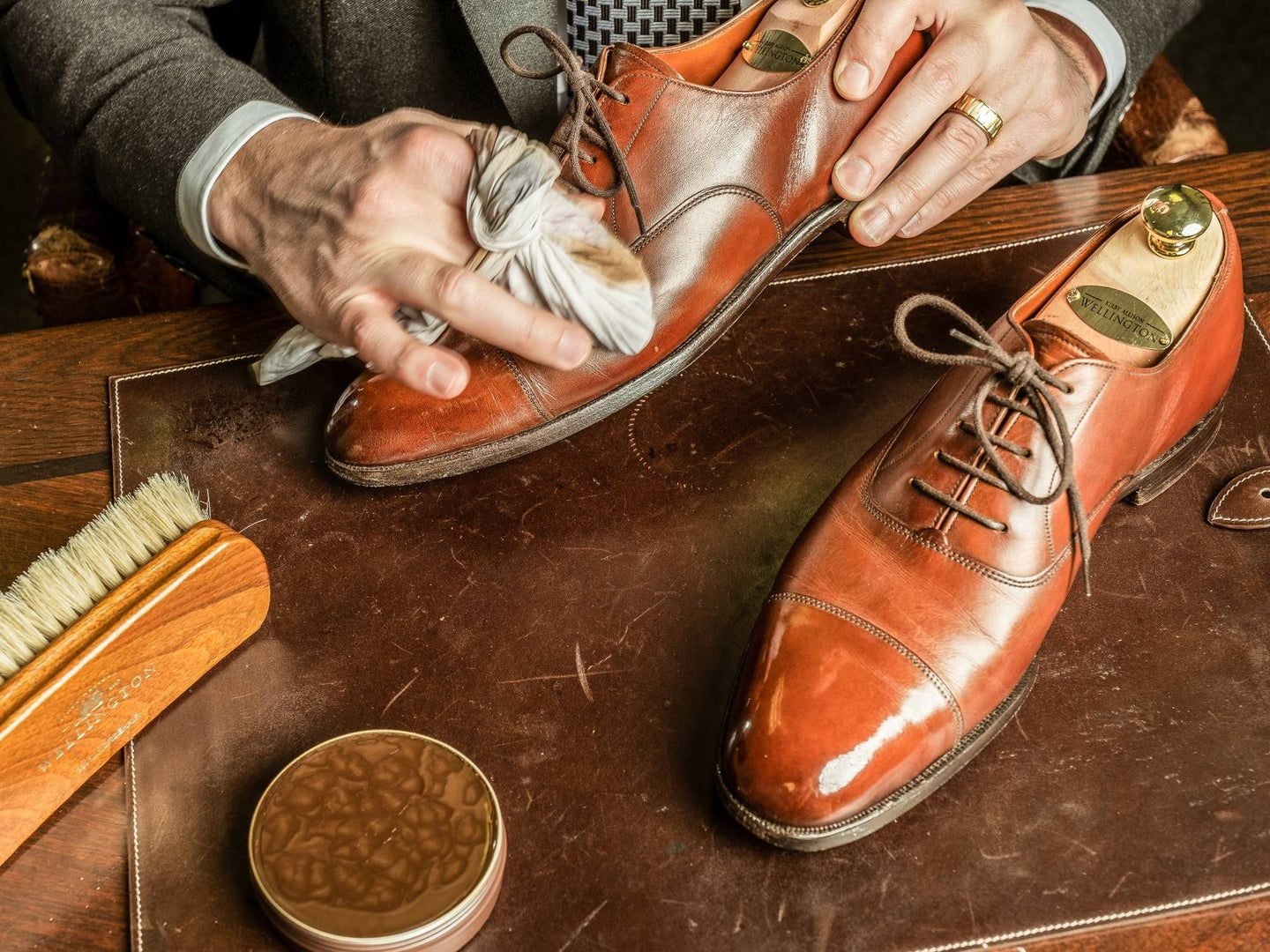 Hands polishing fancy leather shoes on a fancy wooden table.