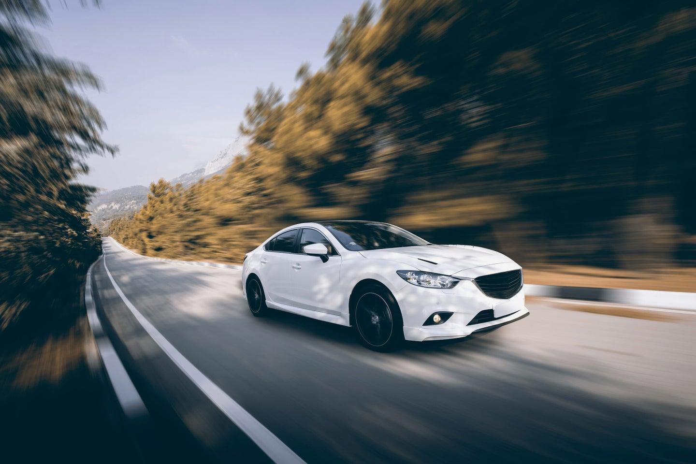 White car speed driving on asphalt road at daytime